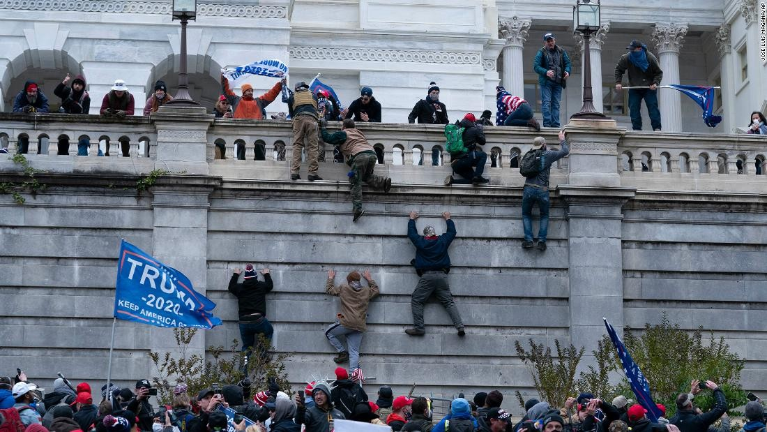Antifa rioters scaling wall at Capitol Building in January 6, 2021 DC Riot.